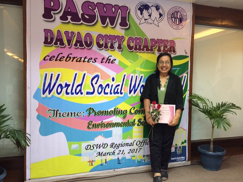 Social worker standing in front of a poster for World Social Work Day 2017 in the Philippines