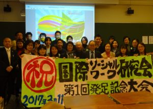 Attendees holding a banner at the launch of the The Japanese Association For The Study Of International Social Work