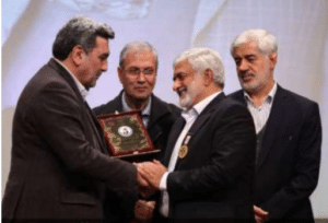 Tehran's Mayer is handing in the plaque of the event to Dr Vaez Mahdavi- Former ministry of Labor, co- op, and Social welfare and deputy of Tehran Municipality observing.